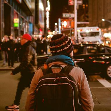 Ein junge Frau geht unglücklich im Ausland durch eine Stadt